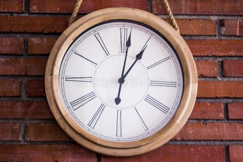 Close–up of a wooden wall clock with roman numerals hanging in a red brick wall. stock photo