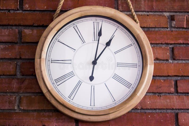 """Close†""""omhoog van een houten muurklok die met roman cijfers in een rode bakstenen muur hangen stock foto"""