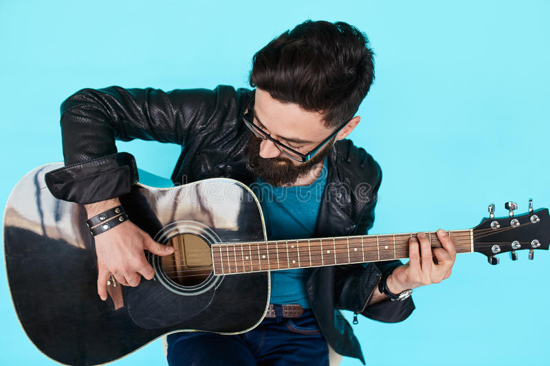 Close Bearded hipster man playing on acoustic guitar. royalty free stock photo