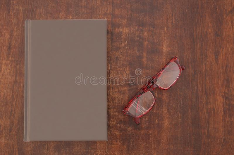 Close book with empty cover and a pair of glasses on a wooden table royalty free stock photography