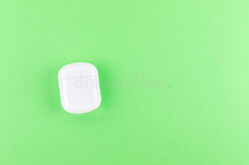 Close case for Airpods wireless headphones. Close charging case for Airpods wireless Bluetooth headphones for smartphone on green background, New Airpods female royalty free stock photography