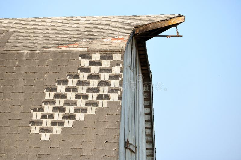 Barn and Severe Shingle Damage. Close detailed view of an old traditional North American wooden barn that has extensive shingle damage to the roof stock photos