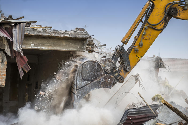 Close of excavator arm demolishing. Barracks for new construction project. Made with shallow depth of field stock photo