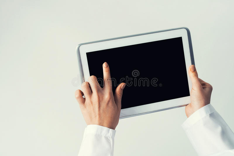 Close of female doctor hands working with tablet pc computer. Tablet pc device with blank screen in hands of doctor royalty free stock image