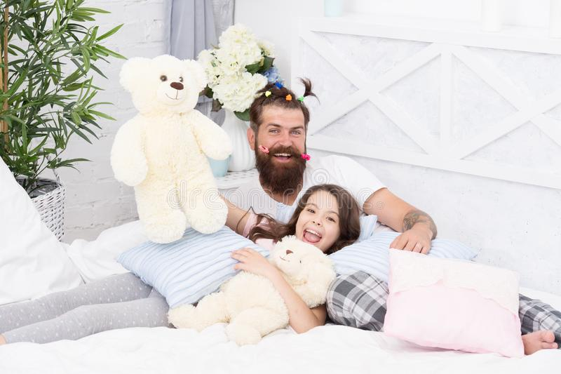 Close friends. Dad and girl relaxing in bedroom. Pajamas style. Father bearded man with funny hairstyle ponytails and. Close friends. Dad and girl relaxing in royalty free stock photography