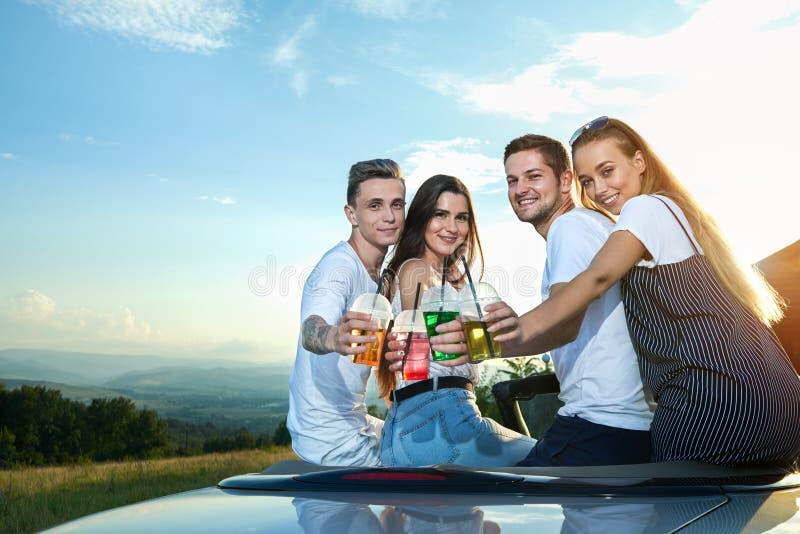 Handsome men and girls sitting on cabriolet, clinking lemonade glasses. stock images
