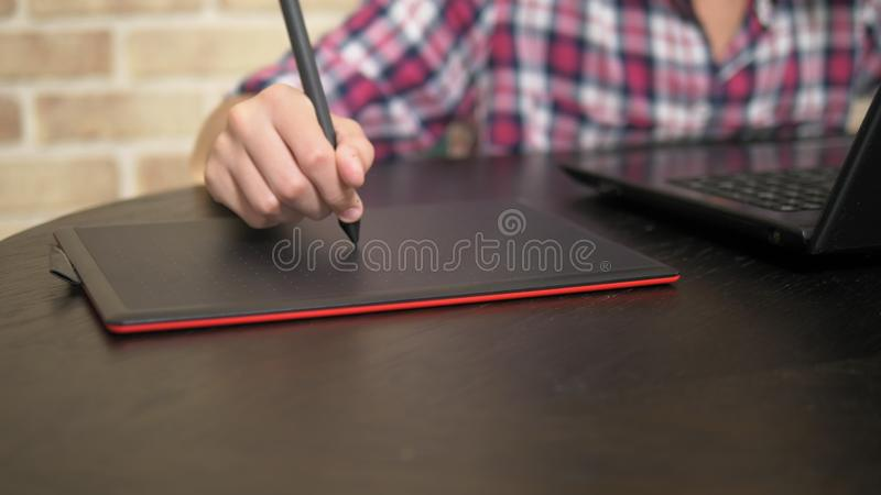 Close. Hand of a teenager boy in a plaid shirt using a stylus. works on a graphic tablet royalty free stock images