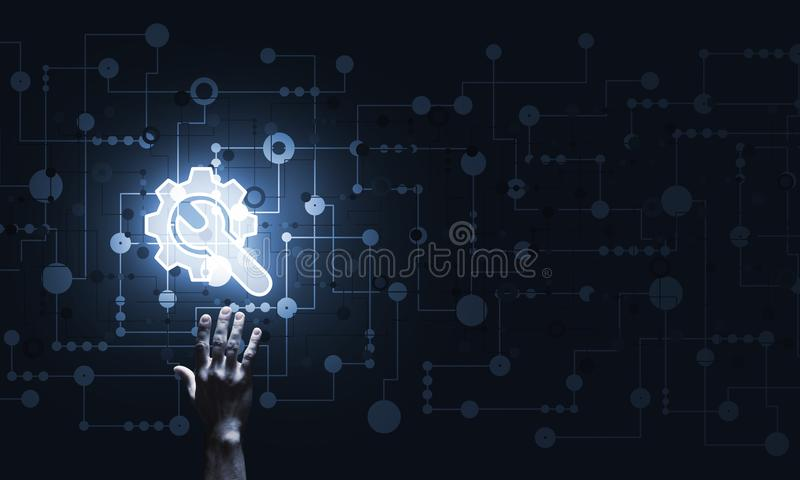 Technology conceptual image with gear digital symbol on dark background. Close of human hand touching with finger setting glowing icon royalty free stock image