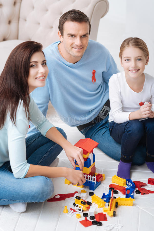 Close knit pleasant family enjoying their time together. Playing with the meccano. Close knit delighted joyful family sitting on the floor near the toys from the stock photos