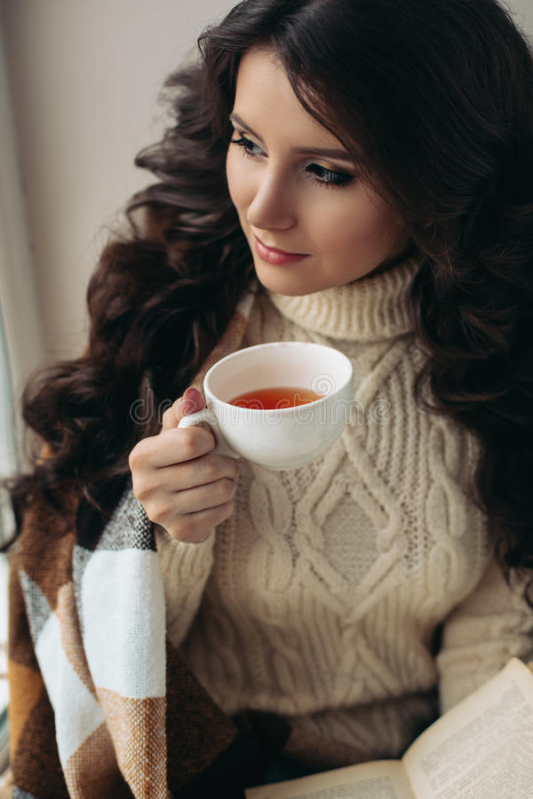 Close large portrait of a brunette drinking tea from a white mug beautiful, girl covered by a blanket. The warm tones in royalty free stock photos