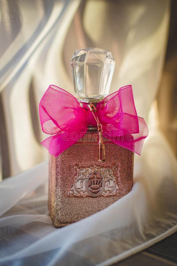Close Photograph of Glitter Pink Fragrance Bottle With Red Ribbon royalty free stock photo
