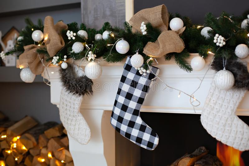 A close picture of beautifully decorated white Christmas socks hanging on fireplace waiting for presents. Christmas socks hanging stock photography