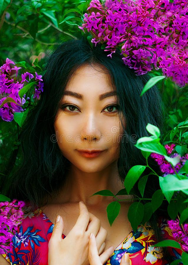 Close portrait of asian woman with pink flower outdoors. Beautiful portrait of asian woman with pink flowers outdoors in the garden stock photo