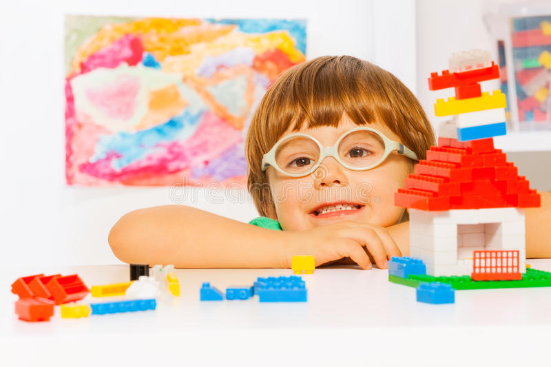 Close portrait of boy in glasses with blocks. Close portrait of clever looking little preschool boy in glasses playing with plastic blocks constructing simple royalty free stock images