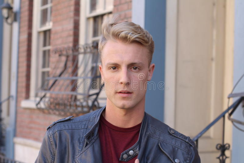 Close portrait of handsome adult blonde man, with blured urban classic background stock image