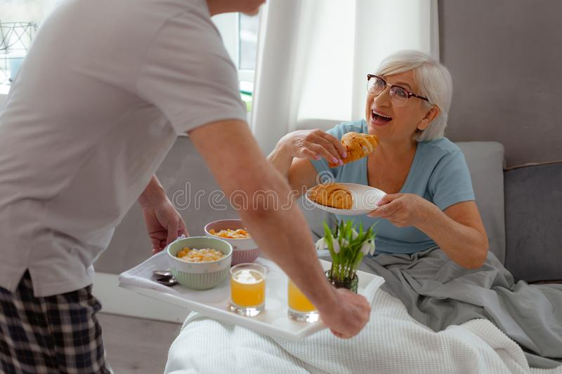 Close portrait of lady going to eat a freshly-baked croissant royalty free stock image
