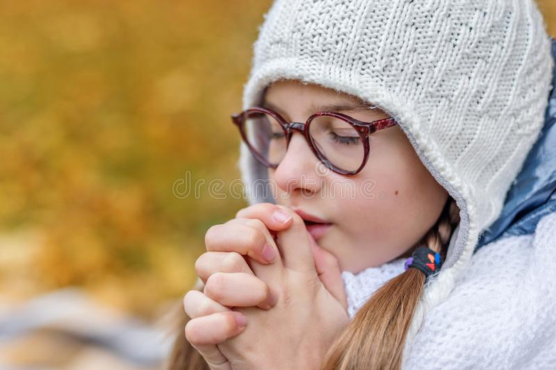 close portrait of little beautiful cute girl teenager with glasses and cozy scarf praying makes a wish stock images
