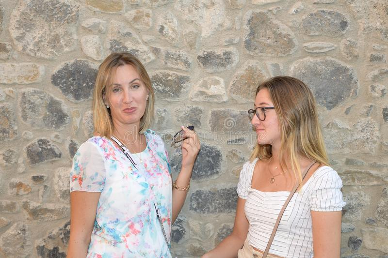 Close portrait of two women with a rustic stone wall in the background royalty free stock photo