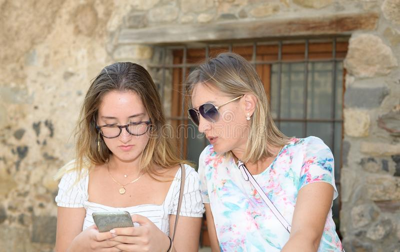 Close portrait of two women sitting and finding on line content on their smart phones on a street of a medieval village royalty free stock image