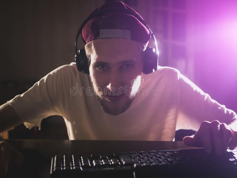 Close portrait of young bearded man playing video game on a computer at home in night stock image