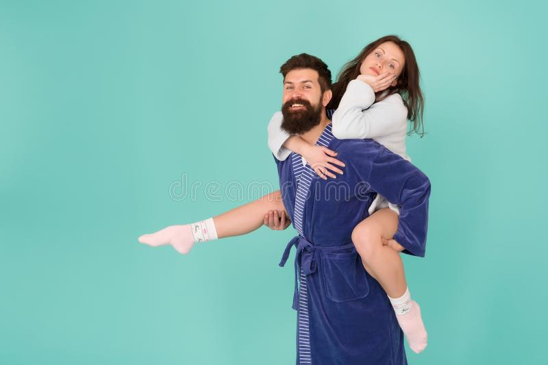 Close relationship. Handsome young man giving his girlfriend piggyback ride. Couple in bathrobes having fun turquoise. Close relationship. Handsome young men stock images
