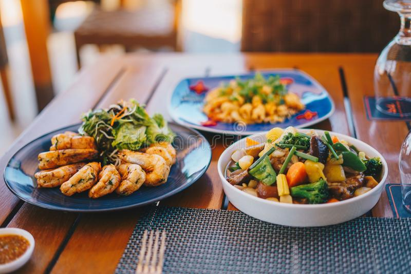 Close shot of a dish with shrimps near a salad on a wooden table  and a blurred background royalty free stock images