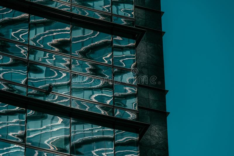Close shot of a glass building with a security camera and a blue sky in the background royalty free stock photos