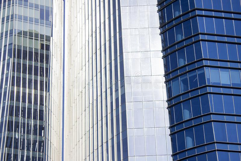 Close shot of a pair of twins corporate blue office buildings with a striped design. Both of them with a blue front fa?ade. Two different blue glass window royalty free stock photo