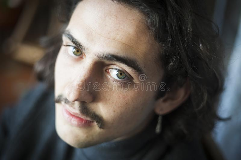 Long haired young man with moustache and ear ring portrait. Close shot portrait of a white young man with blue eyes, moustache, long hair and ear ring stock photos