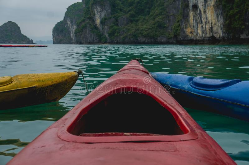 Close shot of a red canoe on the water with a mountain in the distance stock photography