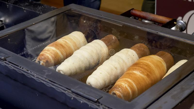 Close shot of trdelnik, a spit cake, cooking in a shop at prague royalty free stock photo