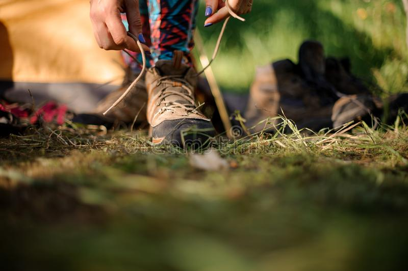 Close shot of woman tying hiking boots. Close shot of woman with blue fingernails tying brown hiking boots stock image