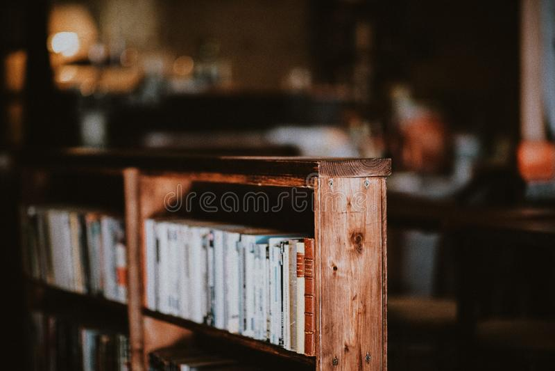 Close shot of a wooden bookshelf with a blurred background. A close shot of a wooden bookshelf with a blurred background stock photos
