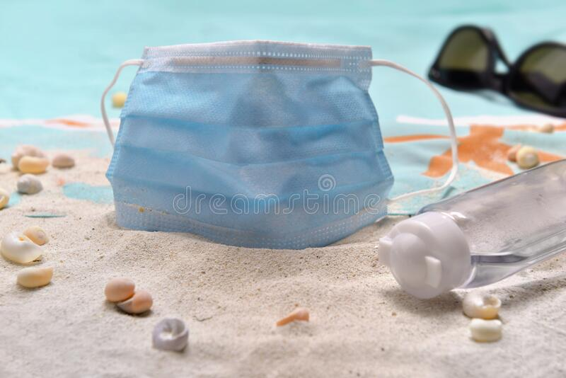 blue surgical mask and hand sanitizer on the beach - concept vacation with royalty free stock photo