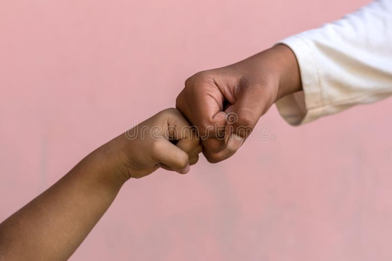 Both hands fist against the pink wall. stock images