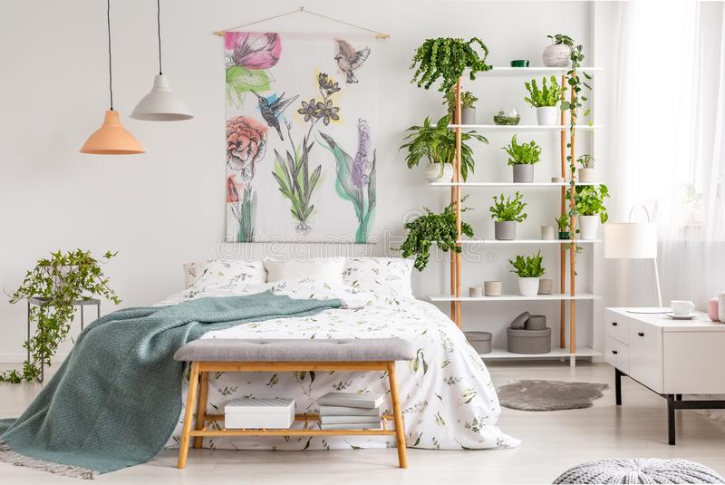 Close to nature bright bedroom interior with a bed covered with white sheets and marine blanket. Green plants on shelves next to t. He bed. Real photo stock image