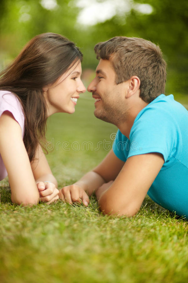 Close to you. Vertical image of a flirting couple lying on the lawn on a sweet summer day stock images