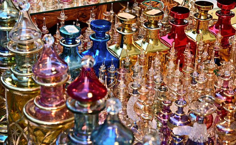 Close together standing richly decorated and colored perfume flacons made of glass in the light of the setting sun. royalty free stock photography