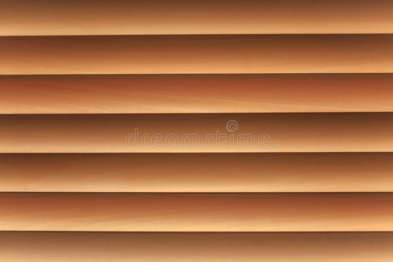 Close un wooden brown jalousie. Texture of louver or jalousie, sunlight through the jalousie stock photography