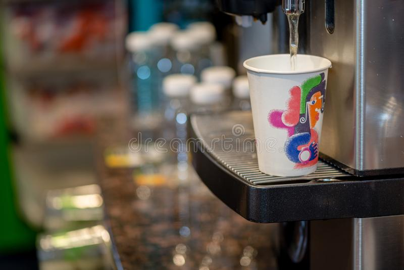 Close uo of the coffee machine fills the hot water in a colored stock image
