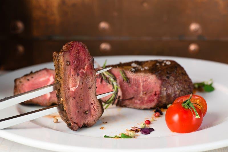 close-up één rundvleeslapje vlees met kruiden bij een plaat royalty-vrije stock afbeelding