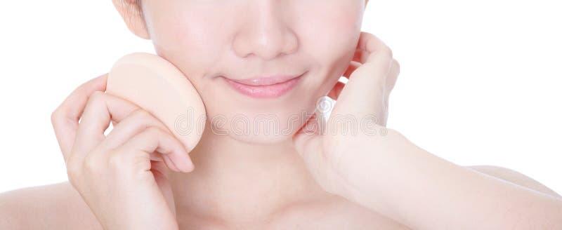 Close-up красотки прикладывая учредительство губкой стоковая фотография