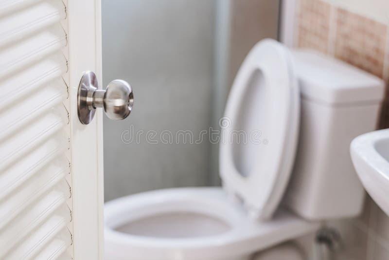 Close-up, abertura da porta do toalete, com mercadorias dos artigos de papelaria, foco seletivo no botão de porta foto de stock royalty free