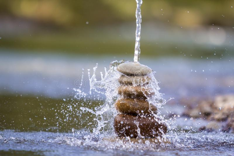 Close-up abstract image of water pouring down on rough natural brown uneven different sizes and forms stones balanced like pyramid. Pile landmark on blurred royalty free stock photos