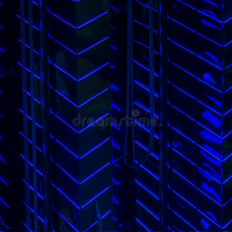 Close-up abstract of pattern of bright blue led backlight walls of high glowing building, modern lighting of buildings. Close-up abstract of pattern of bright stock photography