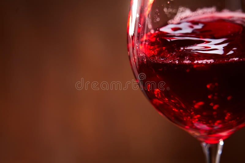 Close-up of the abstract splashing of the red wine in the fragile wineglass on the brown wooden background. royalty free stock images