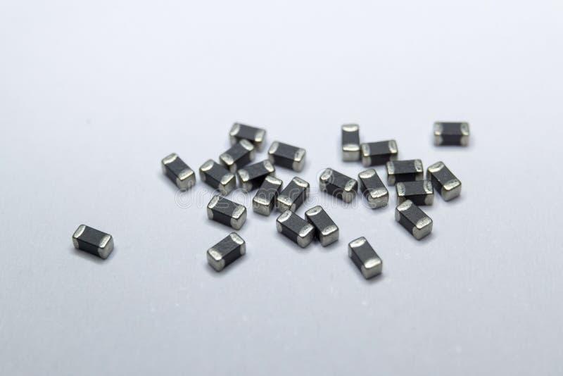 Close-up abstrato de cinzento dispersado 0402 componentes da eletrônica de poder do grânulo de ferrite da microplaqueta da montag foto de stock