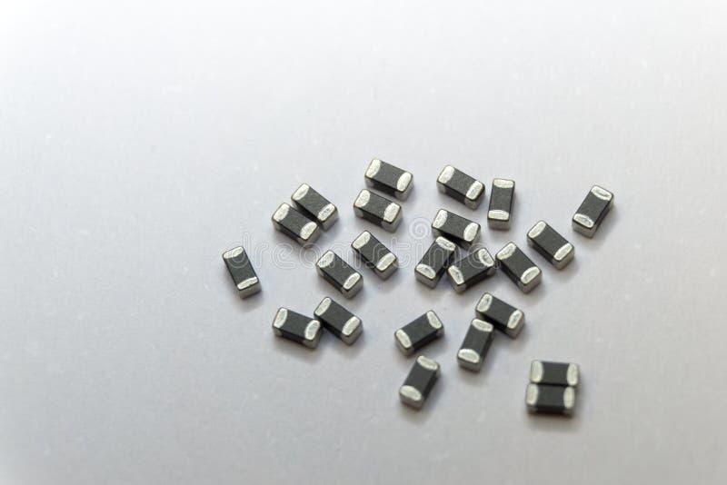 Close-up abstrato de cinzento dispersado 0402 componentes da eletrônica de poder do grânulo de ferrite da microplaqueta da montag imagens de stock