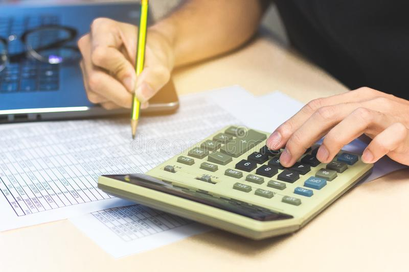Close-up accounting man hands pressing calculator buttons and h royalty free stock images