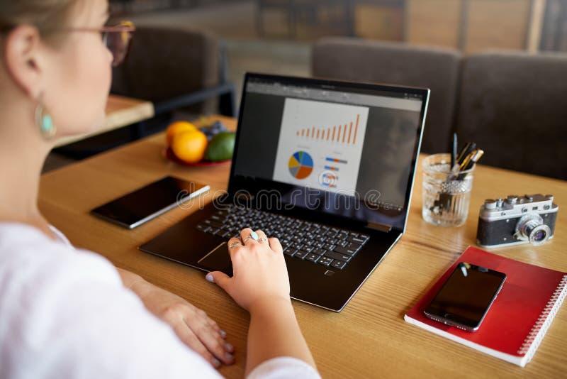 Close-up achtermening van het jonge bedrijfs of studentenvrouw werken bij koffie met laptop computer, het typen, die het scherm b royalty-vrije stock fotografie